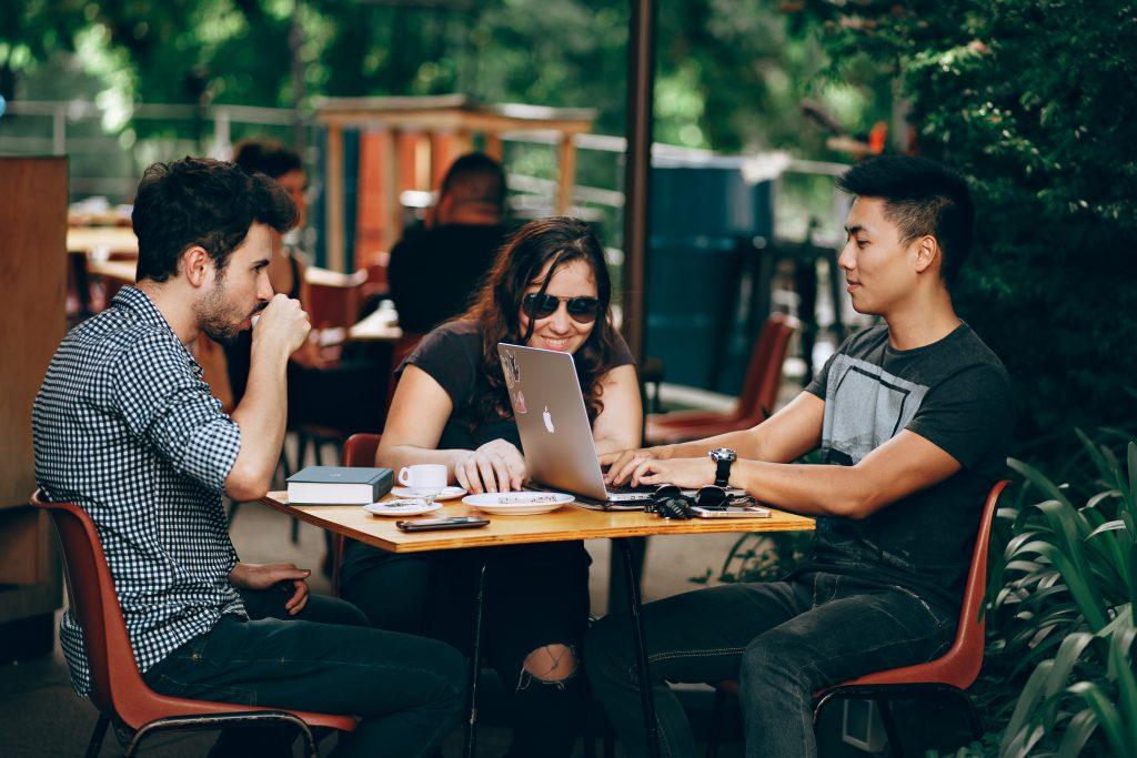 Grupo de jovens conversando em uma mesa de um café, olhando para uma tela de notebook