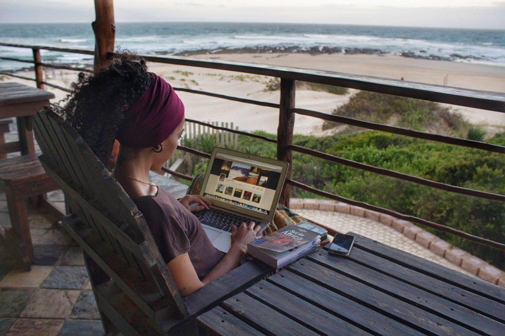 mulher digitando no notebook na frente da praia